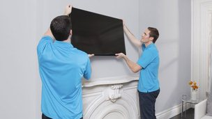 Handy tradesmen fitting a television