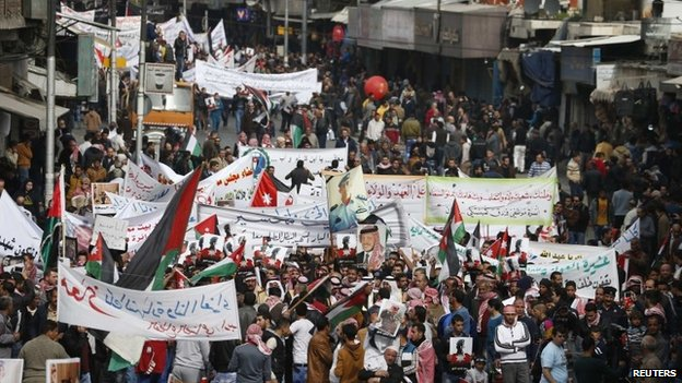 Jordanian protesters hold up pictures of Jordan's King Abdullah and Jordanian pilot Moaz al-Kasasbeh, as they chant slogans during a march after Friday prayers in downtown Amman, 6 February 2015