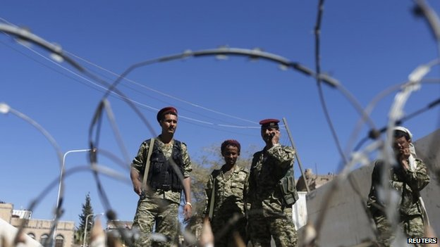 Houthi militiamen and soldiers stand behind a roadblock in Yemen
