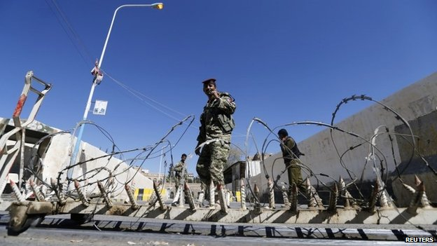 Houthi militiamen and soldiers stand behind a roadblock at the scene of a blast near the republican palace in Sanaa