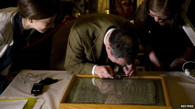 A parliamentary archive conservator examines the Salisbury copy of the Magna Carta