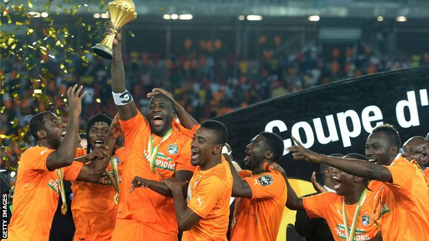 Yaya Toure celebrates and holds the trophy with his Ivory Coast team-mates