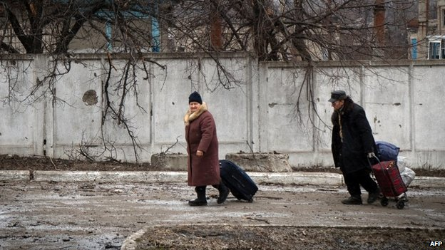 People walk with their belongings on February 7, 2015 in the eastern Ukrainian town of Vuglegirsk in the Donetsk region