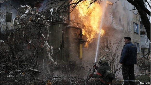 A firefighter works to extinguish a fire at a residential block, which was damaged by a recent shelling according to locals, on the outskirts of Donetsk.
