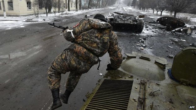 Pro-Russian separatist fighter jumps from an armoured vehicle near a destroyed Ukrainian tank in Uglegorsk, 6 kms southwest of Debaltseve on 9 February 2015