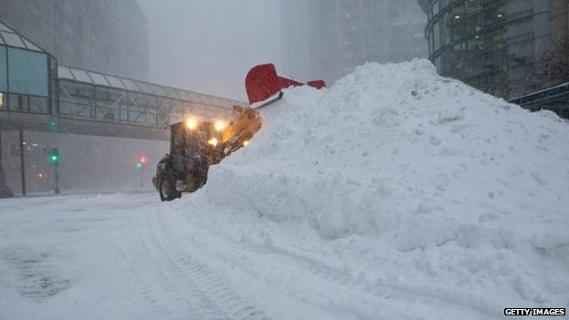 Snow ploughs work during a blizzard to clear the streets in the Back Bay neighbourhood in the early morning on Boston, Massachusetts 27 January 2015