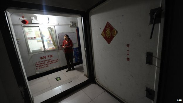 A resident standing at the entrance to underground housing inside an old civil defence shelter