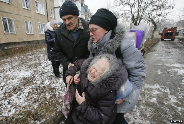 An elderly woman is comforted after her block in Donetsk is hit by shelling (9 Feb)