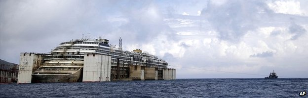 The wreck of the Costa Concordia is held up by giant tanks in the Italian port of Genoa - 21 July 2014