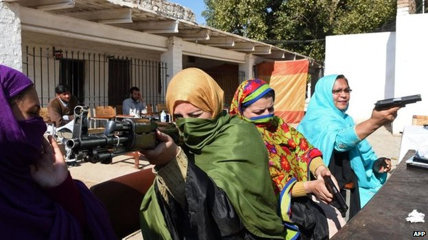 Pakistani teachers handle various firearms during a weapons training session for school, college and university teachers at a police training centre in Peshawar on January 27, 2015