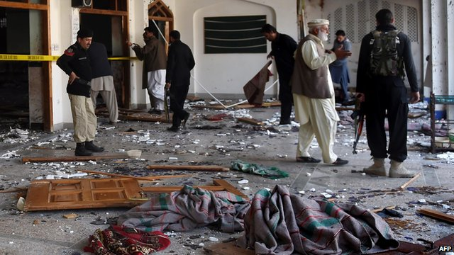 Pakistani security personnel inspect a Shiite Muslim mosque after an attack by Taliban militants in Peshawar on 13 February 2015.