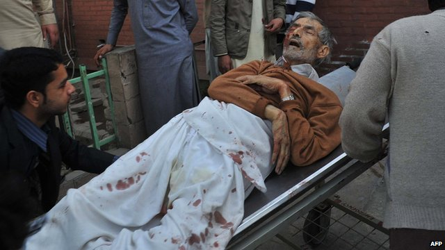 Pakistani residents move an injured worshipper to a hospital following an attack by Taliban militants on a Shia Muslim mosque in Peshawar on 13 February 2015