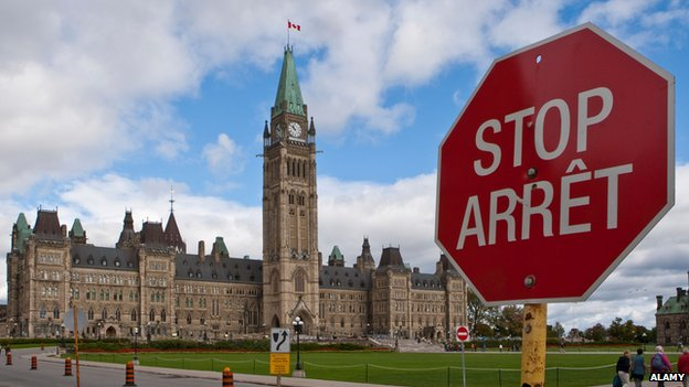 Canada's parliament with a bilingual stop sign outside
