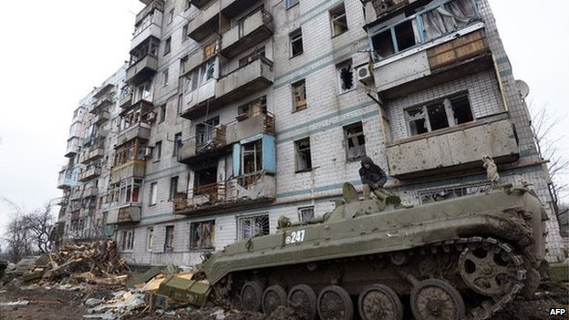 A pro-Russian separatist fighter stands on the top of a tank in front of destroyed buildings in Donetsk