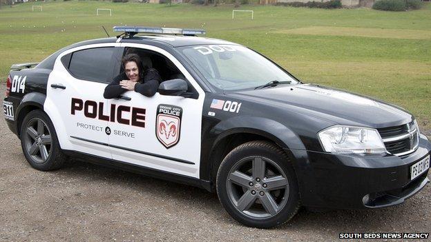 Rachel Sims in a replica police car