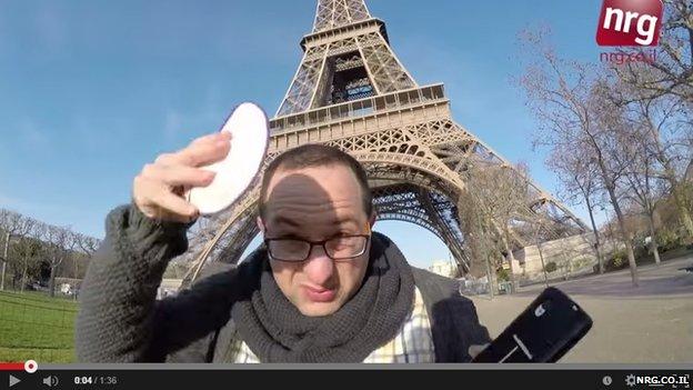A man placing a kippah on his head beside the Eiffel Tower
