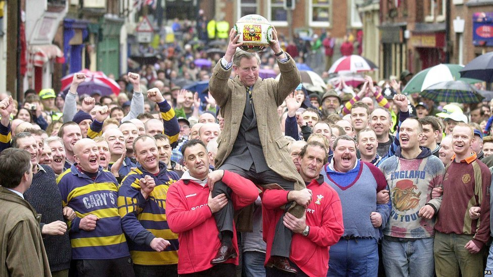 El príncipe Carlos es levantado en hombros para hacer el lanzamiento inicial del partido de fútbol Shrovetide, que es reconocido por la realeza británica.