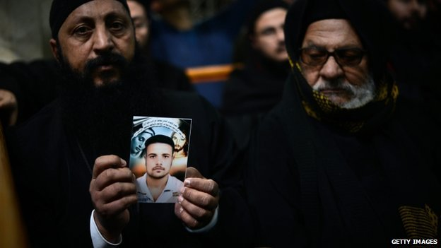 A Coptic clergyman shows a picture of a man whom he says is one of the Egyptian Coptic Christians purportedly murdered by Islamic State (IS) group militants in Libya