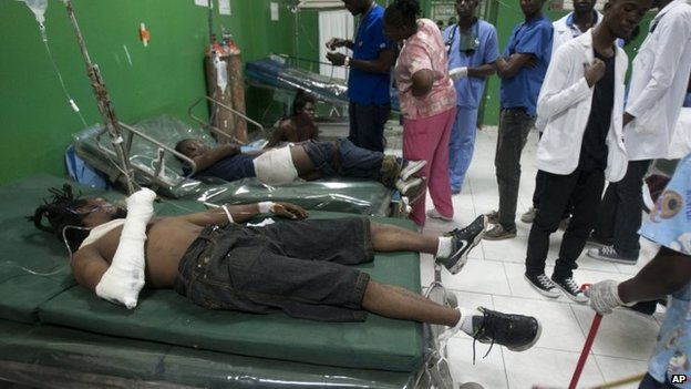 Injured people lie down as they receive treatment at the emergency room of the General Hospital in Port-au-Prince on 17 February, 2015