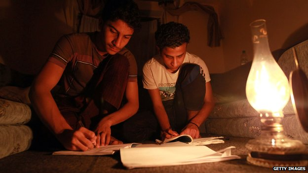 Two boys studying by the light of an oil lamp