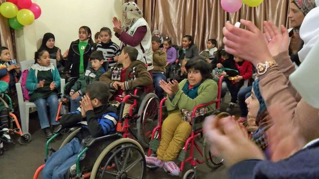 Children in wheelchairs clap along to the music