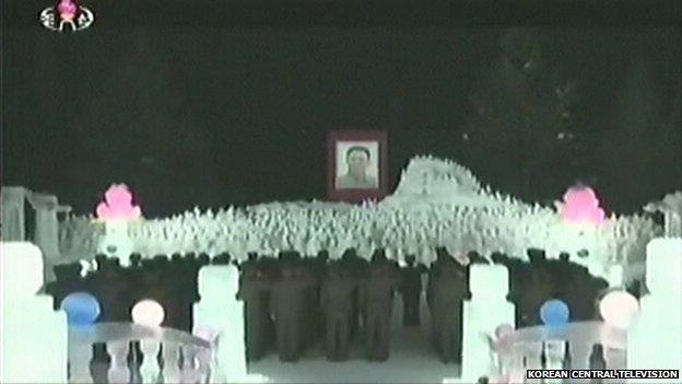 Korean soldiers salute the replica of the Mount Paektu camp