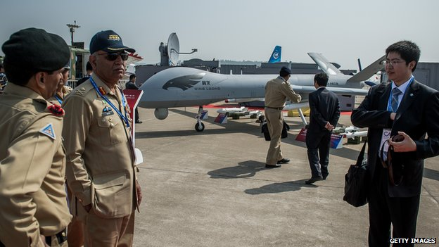 Pakistan Army officers are attended by a Chinese representative as they take a closer look at the 'Yi Long' drone (in background) of China Aviation Industry Corporation (AVIC) during the 9th China International Aviation and Aerospace Exhibition in Zhuhai on November 13, 2012