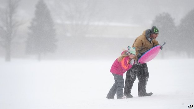 Jeff Guier uses a sled to shield his daughter, Rhyann, after sledding at Helfrich Hills Golf Course, Wednesday, Feb. 18, 2015, in Evanville, Indiana