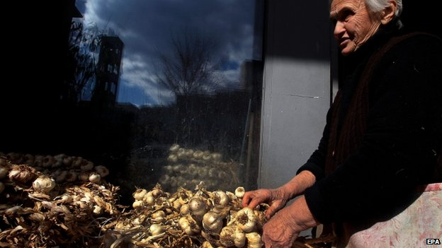 An elderly Greek woman sells garlic outside a store in central Athens, 19 Feb