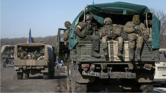 Ukrainian servicemen ride on a military vehicle as they leave area around Debaltseve, eastern Ukraine near Artemivsk, 18 February 2015
