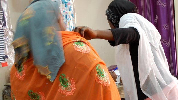 A shop assistant measures a customer at Alhayat Global Synergy in Kano, Nigeria - February 2015