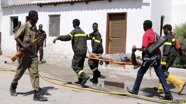 "Rescuers carry a survivor from the scene of a blast at the Central Hotel after a suicide attack in Somalia""s capital Mogadishu February 20, 2015."