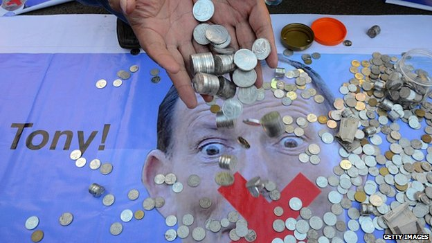 An Indonesian man pours coins from his hands as a 'donation' to Australia's Prime Minister Tony Abbott in Jakarta on 22 February.
