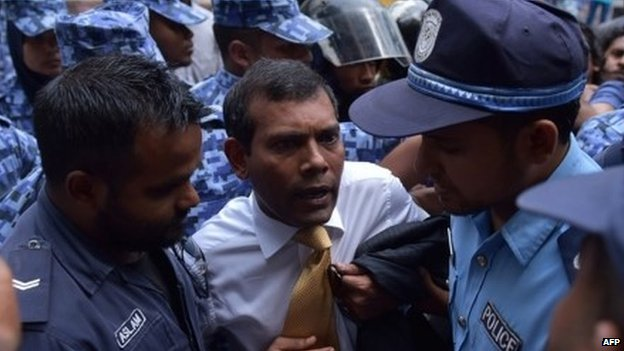 Maldives police try to move former President Mohamed Nasheed (C) during a scuffle as he arrives at a courthouse in Male 23 February 2015.