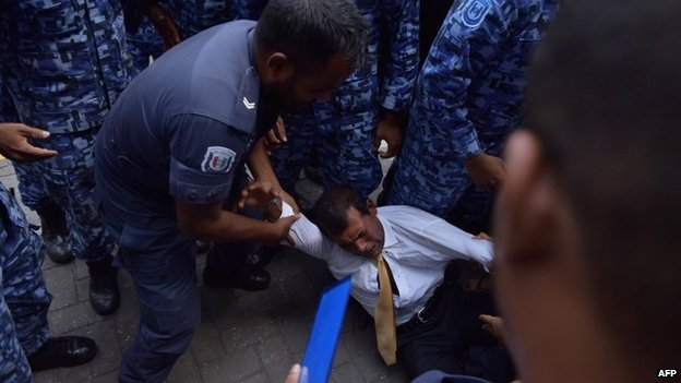 Maldives police try to move former president Mohamed Nasheed during a scuffle as he arrives at a courthouse in Male on 23 February 2015.