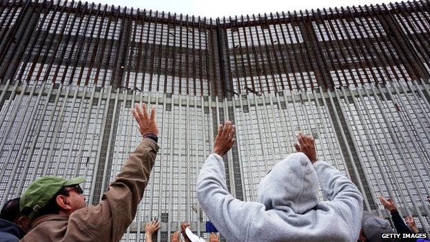 Worshipers participate in a Mass along the US-Mexico border wall on  Tijuana, Mexico 22 February 2015