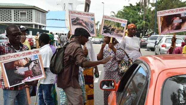 Relatives and friends of victims of the 2010-2011 post-electoral crisis in Ivory Coast holds up images of the slain victims during a protest on February 23, 2015 in front of the Palace of Justice in Abidjan