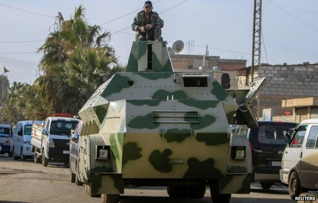 Syrian Kurdish YPG militia fighter sits on an armoured vehicle in Hassakeh, Syria (3 February 2014)