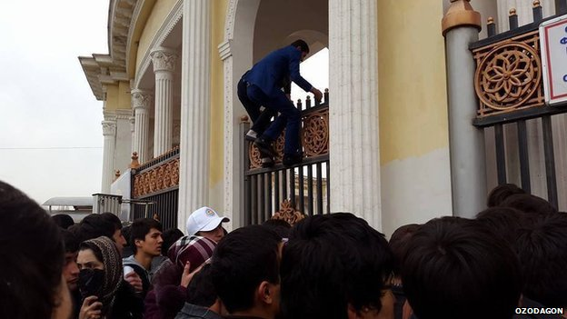 Two men climbing over the railings