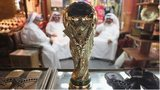 Arab men sit at a shoemaker's stall with a replica of the FIFA World Cup trophy in the Souq Waqif traditional market