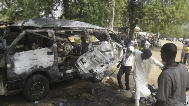 Men inspect a bus following an explosion on the street in Potiskum, Nigeria, on  Tuesday 24 February 2015