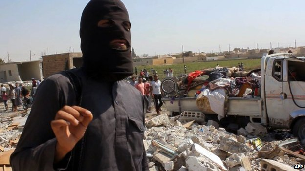 An image grab taken from an AFPTV video on September 16,  2014 shows a jihadist from the Islamic State (IS) group standing on the rubble of houses after a Syrian warplane was reportedly shot down by IS militants over the Syrian town of Raqa