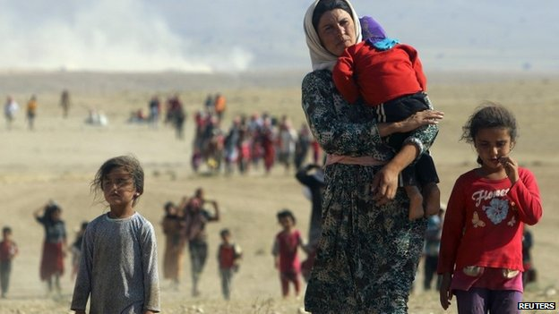 Displaced people from the minority Yazidi sect,  fleeing violence from forces loyal to the Islamic State in Sinjar town,  walk towards the Syrian border on the outskirts of Sinjar mountain near the Syrian border town of Elierbeh of Al-Hasakah Governorate in this August 11,  2014 file photo