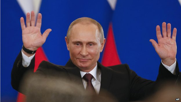 Russian President Vladimir Putin gestures after signing a treaty to incorporate Crimea into Russia in the Kremlin in Moscow on 18 March 2014.
