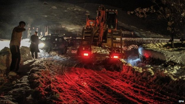 Afghan authorities remove snow from the roads as part of the rescue after an avalanche in the Panjshir valley, Afghanistan, 25 February