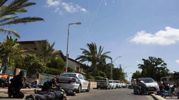 People in Israel's city of Ashkelon take cover as a siren sounds to warn of incoming rockets from Gaza. Photo: July 2014