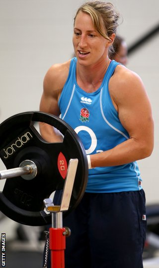 Kat Merchant lifts weights in a gym