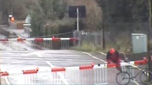 Cyclist climbing over level crossing barrier