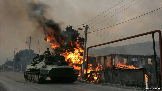 A Russian armoured troop-carrier moves next to a house set on fire by South Ossetian militia on August 18, 2008 in the Georgian village Kvemo-Achebeti