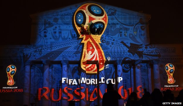 People watch as the facade of the historical Bolshoi Theatre is illuminated with the official emblem of the 2018 FIFA World Cup to be held in Russia in central Moscow in October 2014.